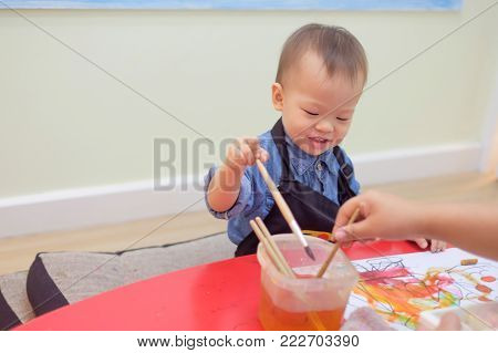 Cute little Asian 18 months 1 year old toddler baby boy child painting with brush and watercolors at art class, kid painting with nursery teacher in a kindergarten, Creative play for toddlers concept
