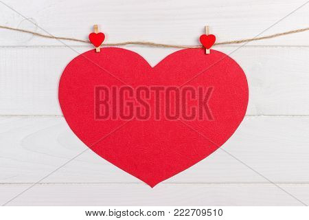 Big love red heart hanging on wooden texture background, valentines day card concept.