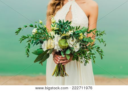 Wedding flowers bouquet in bride's hand. Bride stands on the beach in wedding dress. Bride in wedding dress holding flower bouquet in hand.