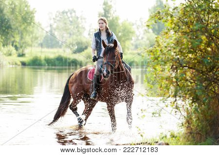Young teenage girl equestrian riding horseback in river at early morning in rays of sunlight. Multicolored vibrant outdoors horizontal summertime image with backlight and vintage filter. poster