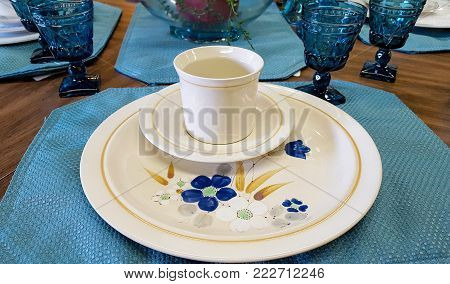 floral place setting with glass stemware on place mat and wood table