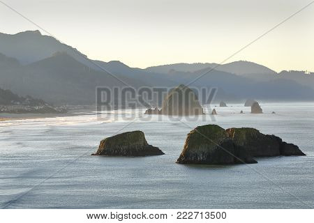 Oregon Coast, Cannon Beach, Dawn. High angle view of Cannon Beach at dawn with famous Haystack Rock in the background. Oregon, United States.
