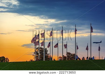 Washington D.C., USA, october 2016: sunset over waving american flags with tourists and an airplane landing in background