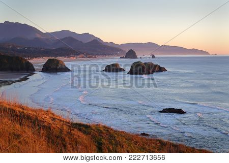 Oregon Coast, Cannon Beach, Dusk. Ecola State Park at dusk. Cannon Beach with famous Haystack Rock in the background. Oregon, United States.