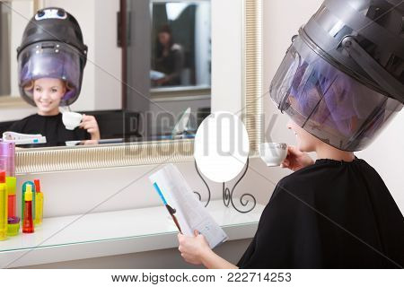 Young woman female client reading magazine in hairdressing beauty salon. Girl in hair rollers curlers with hairdryer dryer relaxing by hairdresser hairstylist.