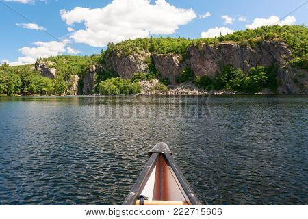 Cliffs with trees and canoe front on the Bon Echo lake