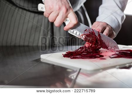 Closeup of hand with knife cutting fresh vegetable. Young chef cutting beet on a white cutting board closeup. Cooking in a restaurant kitchen.