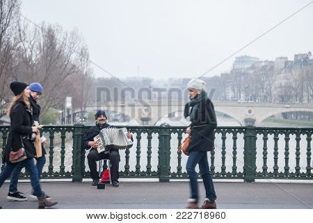 PARIS, FRANCE - DECEMBER 20, 2017:  Accordionist plating accordion on the Arcole bridge in Paris, over the Seine river. Accordion music is supposed to be one of the symbols of Paris lifestyle