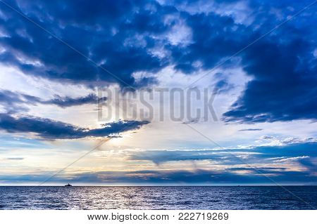 The blue beautiful landscape of the sky with graceful clouds blockaded the bright sun over the sea, the ship in the distance on the horizon. Beautiful colorful sunset on the Black Sea, Sochi, Russia. poster