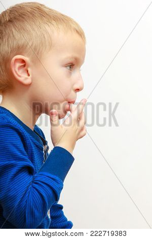 Portrait of cute blond boy child kid preschooler licking his fingers. At home.