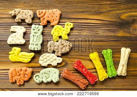 Delicious chewing colored bones and zoological biscuits  for dogs with different tastes on wooden background poster