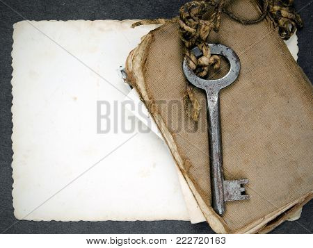 Rusty key, old book and empty photography as a memories metaphor
