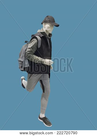 Running male mannequin isolated over blue background. No brand names or copyright objects.