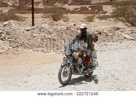 AL HAJARAYN, YEMEN - MAY 11, 2007: A man and his son ride their motorbike in Al Hajarayn, Yemen on May 11, 2007. Among other arabic countries, in 2012 Yemen became a site of civil conflicts, which still continue.