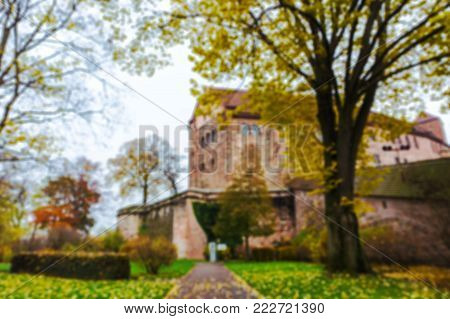 Blurred natural bokeh background of beautiful garden and park view of Nuremberg castle, old historical fortress Kaiserburg, landmark of the historic city center of Nurnberg, Franconia, Germany.