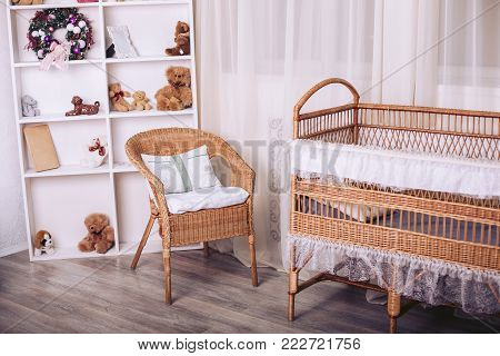 Rattan furniture in the children's bedroom with toys and New Year elements in gentle colors