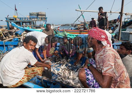 A group of fishermen in a boat prepare fish for sale in the famous fish market of the city on May 12, 2007 in Al Hudaydah, Yemen. Due to the rich with fish species Red Sea, fish markets play a central role in the economic life of Yemen.