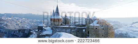 Old fortress and fortifications of ancient sity of Kamianets-Podilskiy, Ukraine. Beautiful panorama of famous medieval fortress under snow.