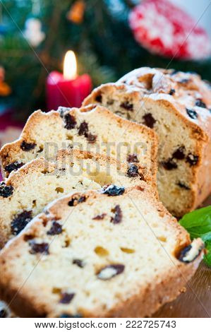 Sliced christmas fruitcake with raisins and mint leaf on christmas background. Colored vertical indoors image.