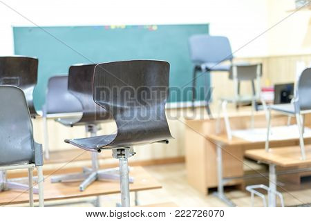 in the classroom, the chairs are on the desks