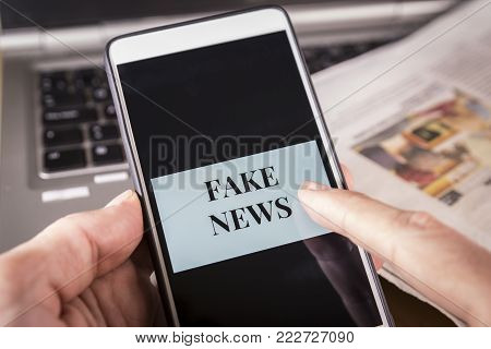 Man's hand holding a smartphone with Fake News words on screen over a newspaper and a laptop. HOAX and Fake news concept.