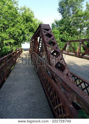 The rusting arch of a road  bridge over a small river in Coldwater, Michigan, USA