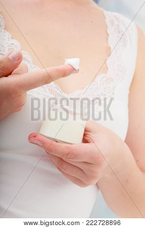 Skincare, beauty treatment. Woman taking care of her dry complexion. Moisturizing cream in female hands in bathroom