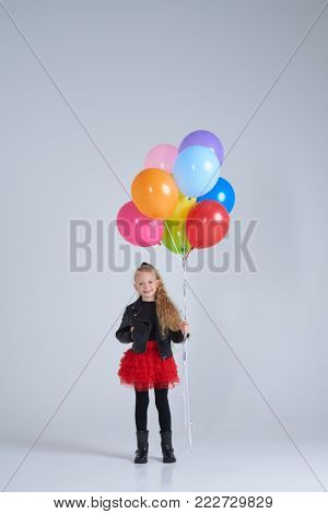 Full-length shot of joyful girl in rock style outfit holding colorful balloons