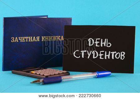 A blue book with an inscription in Russian - a student's record book. Pen, calculator on a blue background. Inscription in Russian - Students Day