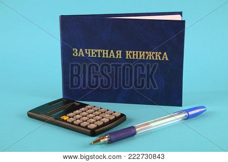 A blue book with an inscription in Russian - a student's record book. Pen, calculator on a blue background. Students Day
