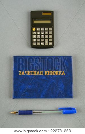A blue book with an inscription in Russian - a student's record book. Pen, calculator against gray background. Students' Day