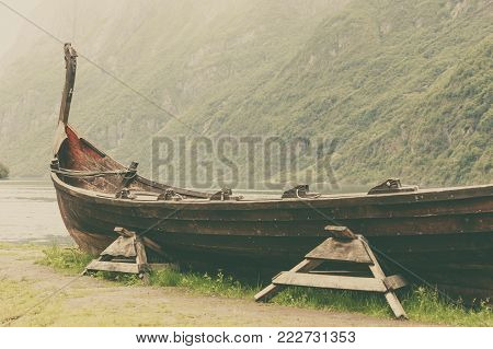 Old wooden viking boat on seashore in norwegian nature. Mountains and fjord Sognefjord. Tourism and traveling concept