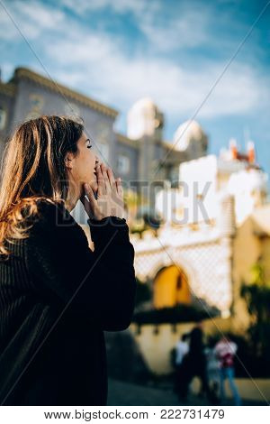 Female tourist admiring popular portuguese historical landmark National Palace of Pena,royal caste of Portugal.Colorful Romanticist architectural wonder.Woman visiting UNESCO World Heritage in Sintra