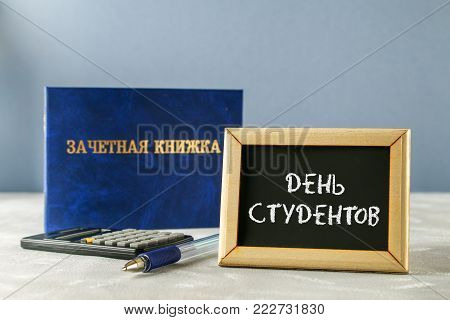 A blue book with an inscription in Russian - a student's record book. Pen, calculator on a gray background. Inscription in Russian - Students Day