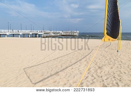 View of a pier and beach volley net at the Brzezno beach in Gdansk, Poland, on a sunny day in the autumn.