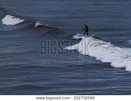 Surfer Holding Oar In Wetsuit Negotiating Waves  On Tynemouth Beach