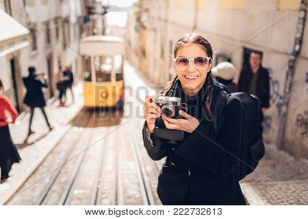 Female traveler woman sightseeing in European capital.Visitor in Lisbon,Portugal.Yellow tram route.Traveling Europe on a budget.Studying abroad.Photography and travel concept