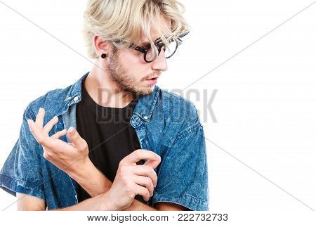Men fashion, accessories, hairstyle, modeling concept. Artistic hipster man wearing jeans outfit and eccentric glasses looking down, hand gesture, studio shot isolated