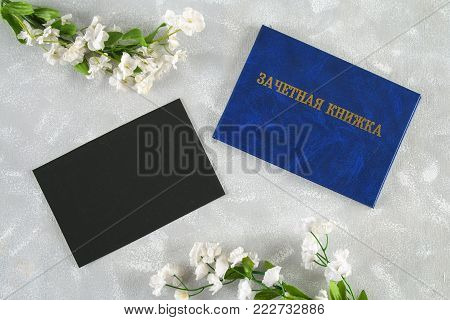 A blue book with an inscription in Russian - a student's record book. White flowers on a gray background. Students' Day. Tatyana's Day. Copy the space