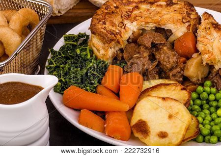 Beef in Stout Pie A Beef in Irish Stout Pie with Pan Haggerty potato with Stout battered onion rings and Sourdough Bread.