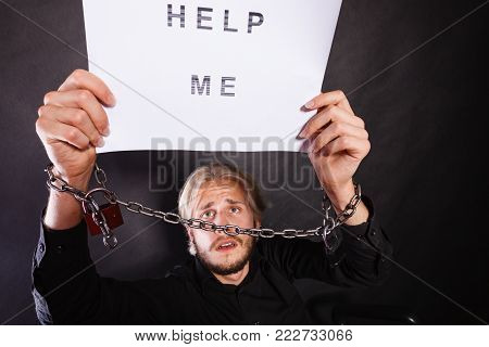 Stress, depression, assistance concept. Scared man with chained hands holding help me sign, studio shot on dark, grunge background
