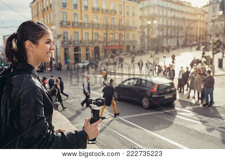 Female professional videographer travel photographer making video in 4K resolution trough of the streets holding 3 axis gimbal stabilizer.Filming with stabilized camera.Travel light equipment