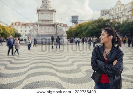 Enjoying beautiful warm and sunny day in Lisbon, Portugal.Sunset sun rays in small narrow street of colorful Lisbon.Experiencing charming european city.Smiling woman admiring Lisbon architecture