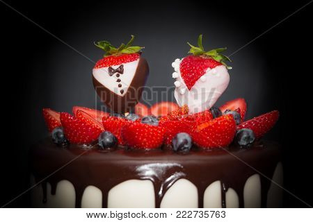Strawberry spotlight couple bride groom luxury wedding drip cake. Confectionery art trend marriage strawberries bridal couple embellishment, chocolate, blueberries and frosting cream. Symbol of love.