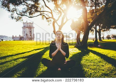 Carefree happy woman practicing yoga and meditation in lotus pose near Torre de Belem.Mindfulness and daydreaming.Enjoying in Lisbon.Sunset in Portugal
