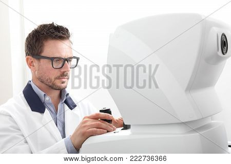 optician with keratometer, optometrist doctor examines eyesight, isolated on white