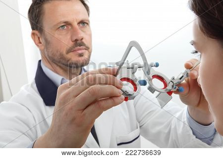 optician hands with trial frame, optometrist doctor examines eyesight, front view isolated on white