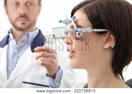 optometrist with trial frame examining eyesight  woman patient in optician office