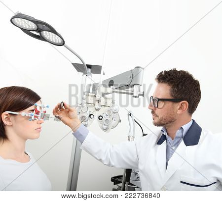 optometrist with trial frame examining eyesight  woman patient in optician office isolated on white