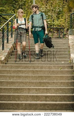 Two young people tourists hiking walking on stairs. Man and woman with trekking poles sticks.